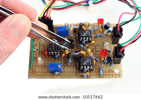 hands holding tweezers adjusting a hand made electronic part - stock photo