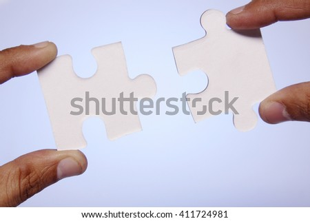 Hands holding two jigsaw pieces - stock photo