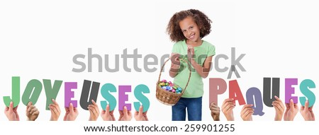 Hands holding up joyeuses pasques against portrait of a cute girl holding a basket full of easter eggs - stock photo