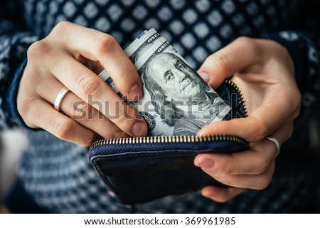 Hands holding us dollar bills and small money pouch - stock photo