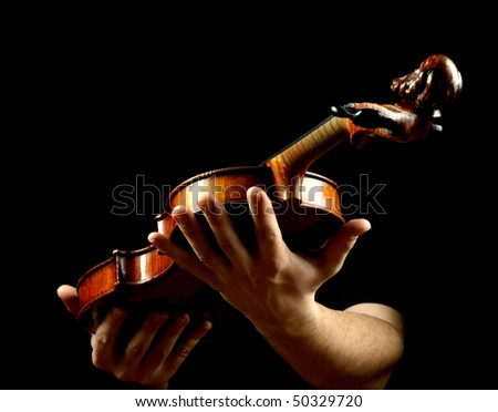 Hands holding violin isolated on black background - stock photo
