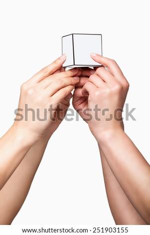 Hands holding white cube on white background - stock photo