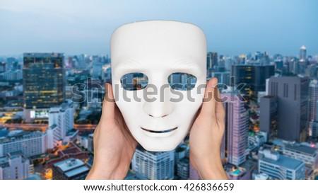 Hands holding white mask on blurred city landscape background. - stock photo