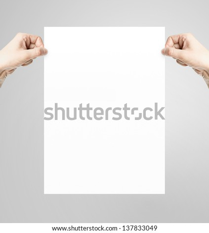 hands holding white paper poster - stock photo