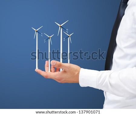 Hands holding wind turbine - stock photo