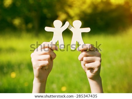 Hands holding wooden little men on natural background. Symbol of friendship, love, teamwork or ecology concept - stock photo