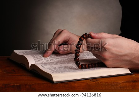 Hands holding wooden rosary over open russian holy bible on grey background - stock photo