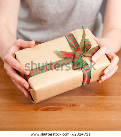 Hands Holding Wrapped Present with Bow - stock photo