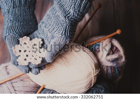 Hands in a grey gloves holding white knitted snowflake as a winter symbol
