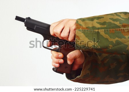 Hands in camouflage uniform reload gun on a white background - stock photo
