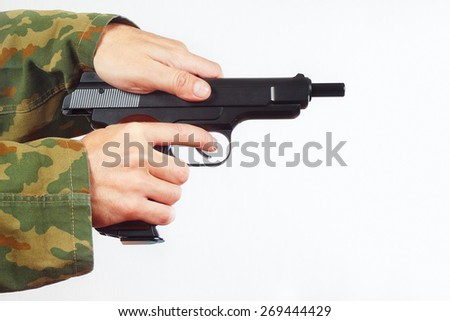 Hands in camouflage uniform reload pistol on a white background - stock photo