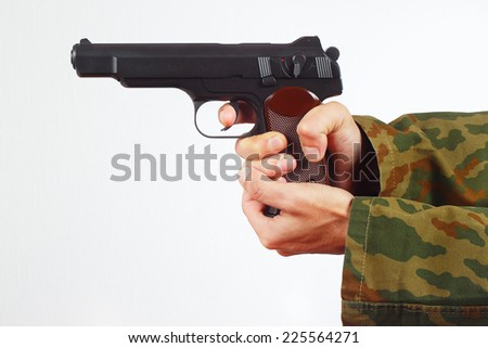 Hands in camouflage uniform with gun on a white background - stock photo