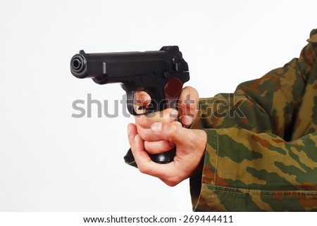 Hands in camouflage uniform with handgun on a white background - stock photo