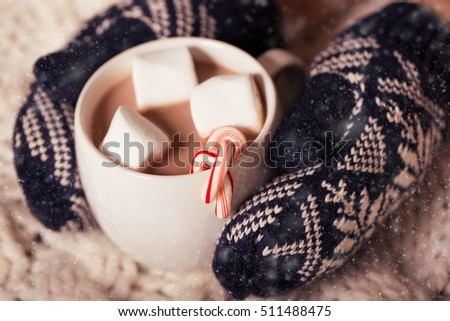hands in cozy mittens holding hot chocolate in the cup with marshmallows and candy canes in snowy weather, christmas and winter time concept