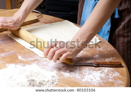 hands in flour closeup kneading dough on table - stock photo