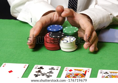 Hands in foreground betting in poker chips - stock photo