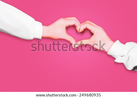 Hands in form of heart isolated on pink background, arms wearing long white sleeves - stock photo