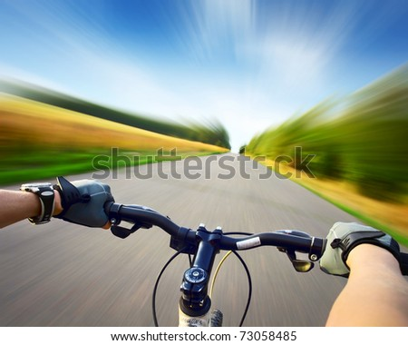 Hands in gloves holding handlebar of a bicycle. Motion blurred asphalt road - stock photo