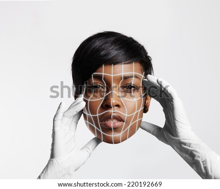 hands in gloves holding woman's face with laser mask - stock photo