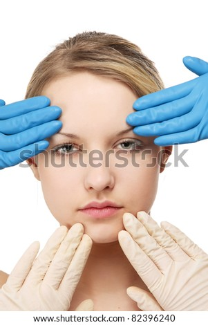 Hands in gloves touching a female face, isolated on white - stock photo
