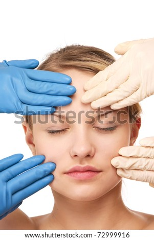 hands in gloves touching the face of a young woman - stock photo