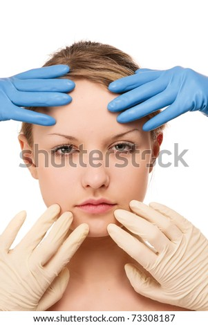Hands in gloves touching young woman's face - stock photo