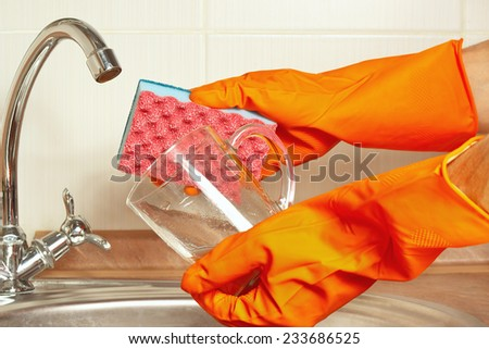 Hands in gloves with sponge and dirty glass over the sink in the kitchen - stock photo