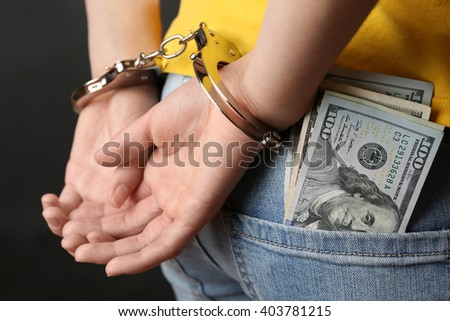 Hands in handcuffs behind back and dollar banknotes on the pocket, close up. Corruption concept - stock photo
