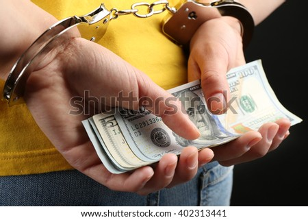 Hands in handcuffs behind back holding dollar banknotes, close up. Corruption concept - stock photo