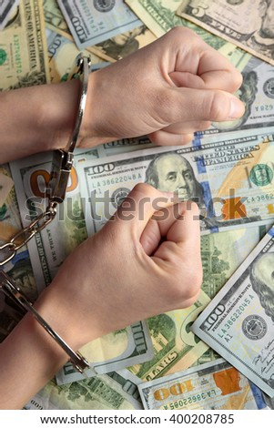 Hands in handcuffs on dollar banknotes. Corruption concept - stock photo