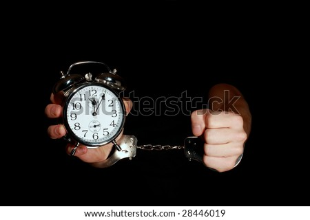 Hands in handcuffs with a clock - stock photo
