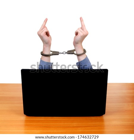 Hands in Handcuffs with Middle Fingers Gestutre behind Laptop Isolated on the White