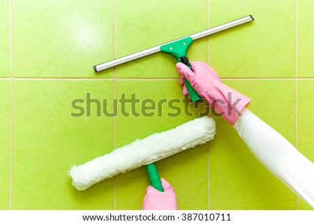 Hands in pink protective gloves cleaning tiles with professionally washer and squeegee. Early spring cleaning or regular clean up. Maid cleans house. - stock photo