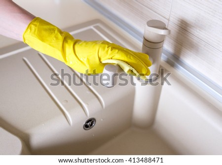 Hands in rubber gloves cleaning the faucet in the kitchen - stock photo