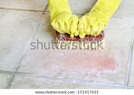 hands in rubber gloves scrubbing the floor - stock photo