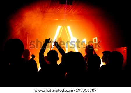 Hands in the air silhouette at nightclub party rave - stock photo