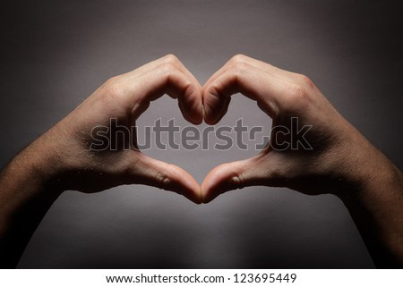 Hands in the shape of a heart - stock photo