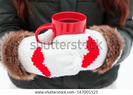 Hands in warm mittens with hearts holding red cup close-up - stock photo
