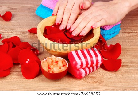 Hands in water with rose petals - stock photo