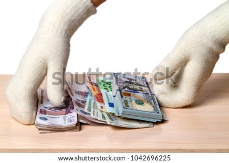 Hands in white knitted mittens and a variety of paper money