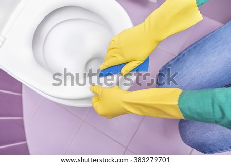 Hands in yellow gloves washing a toilet bowl.