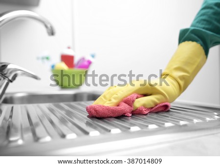 Hands in yellow gloves washing the kitchen sink. - stock photo