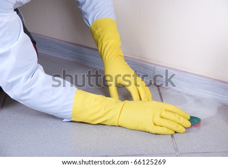 Hands in yellow gloves with sponge, washing floor and plinth