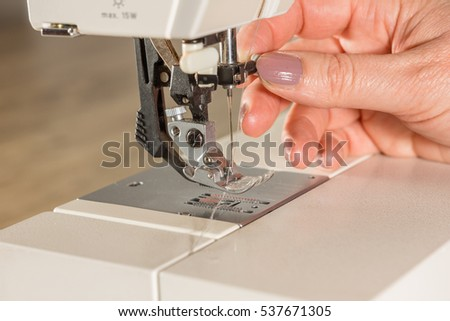 Hands introducing the thread in a sewing machine
