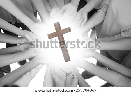 Hands joined in circle holding breast cancer struggle symbol against wooden cross