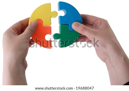 Hands joining slices of a puzzle on a white background - stock photo