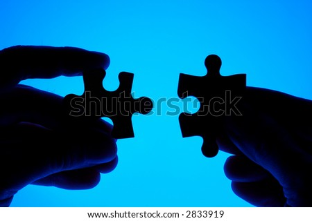 Hands joining two puzzle pieces. - stock photo