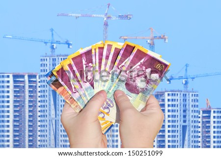 Hands keep banknotes (Shekel israeli) on a building background - stock photo