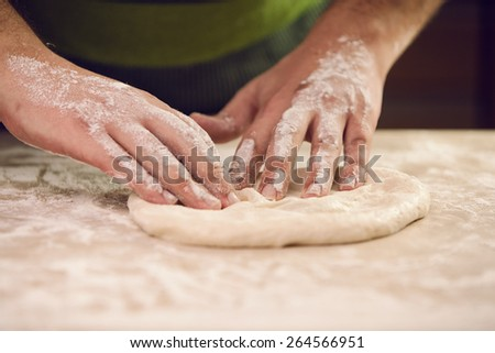 hands knead the dough for pizza making - stock photo
