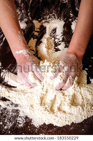 hands knead the dough with flour - stock photo